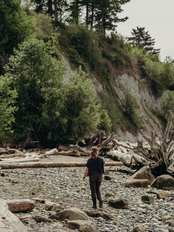 Heidi Gustafson foraging for ochre on a shore with a bluff