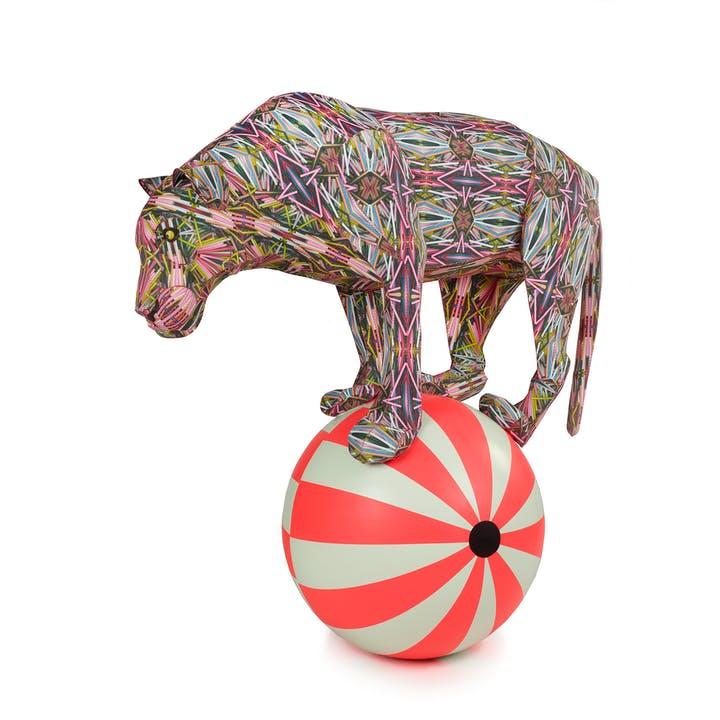 Colorful sculpture of a tiger balancing on a striped ball