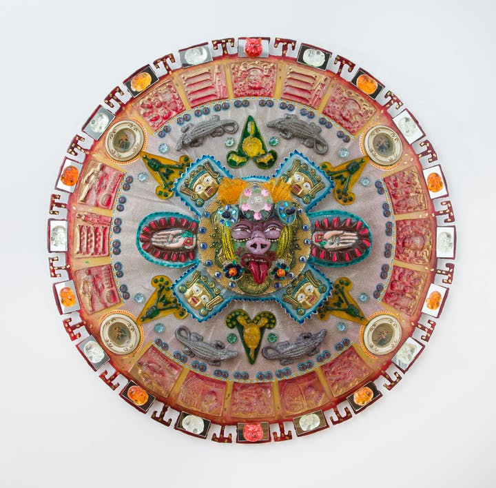 Colorful glass mandala with various faces and animals