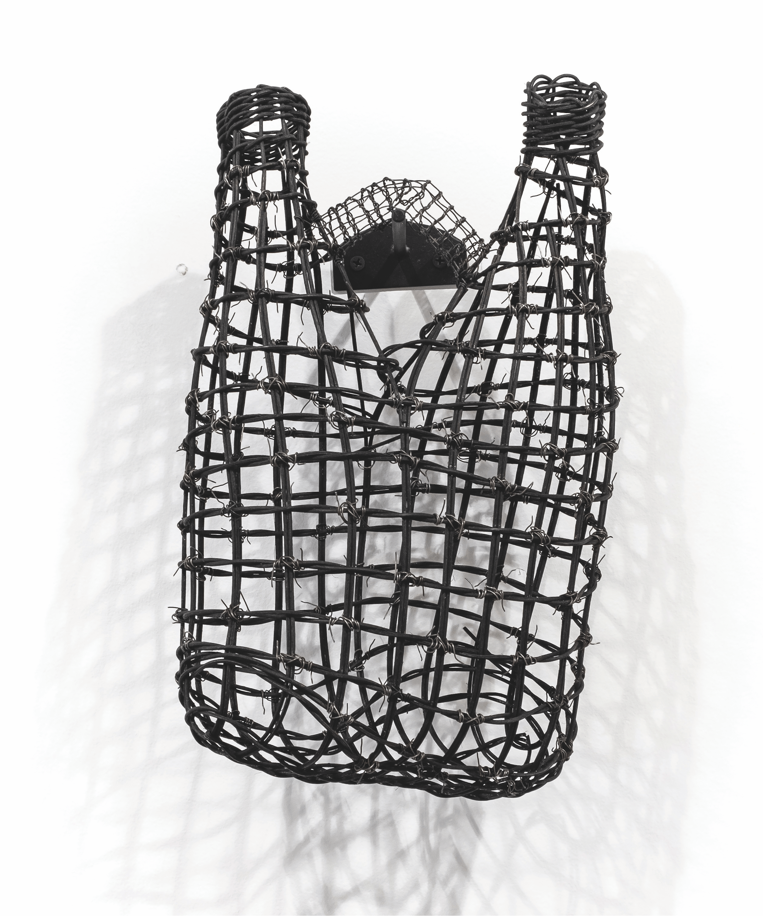 Woven sculpture of two fused bottles connected by a small bridge