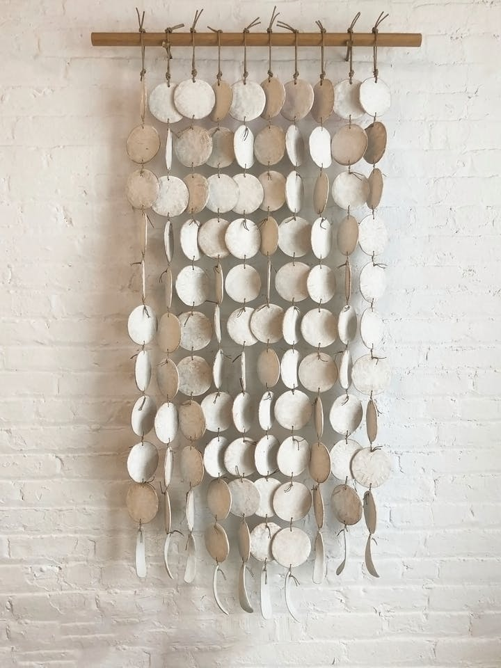 Wall art by Michele Quan featuring hanging discs