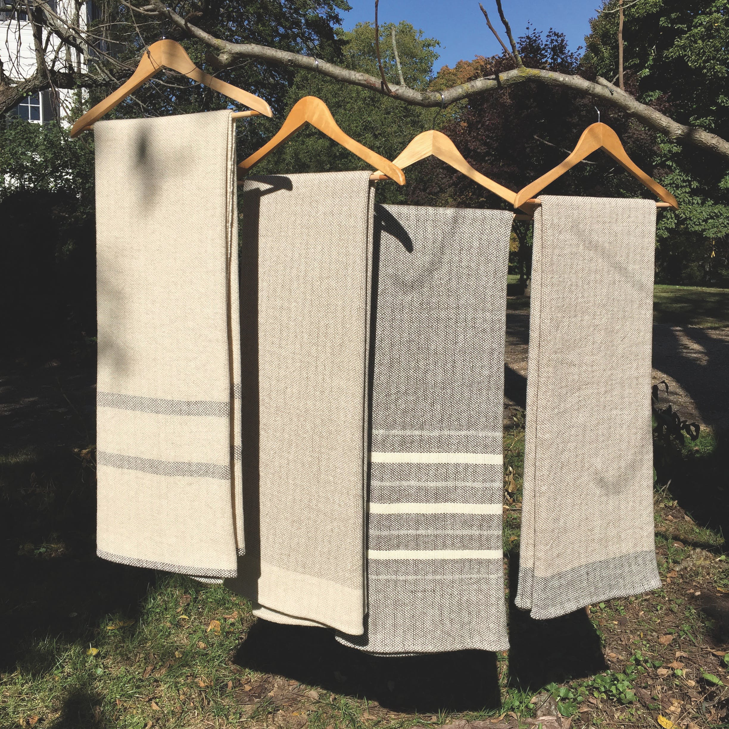 Four gray throw blankets on shirt hangers outside
