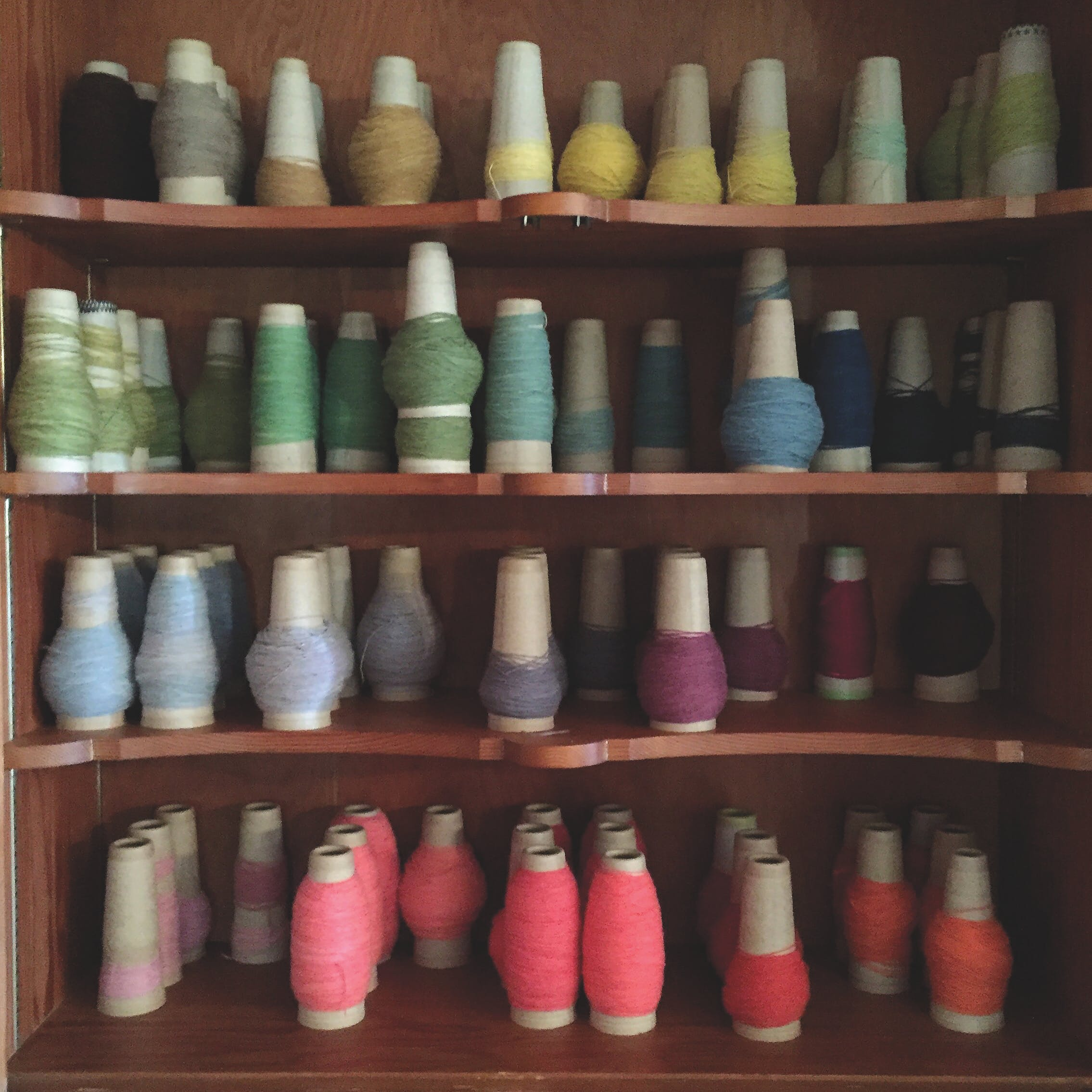 Colorful spools of yarn on shelves