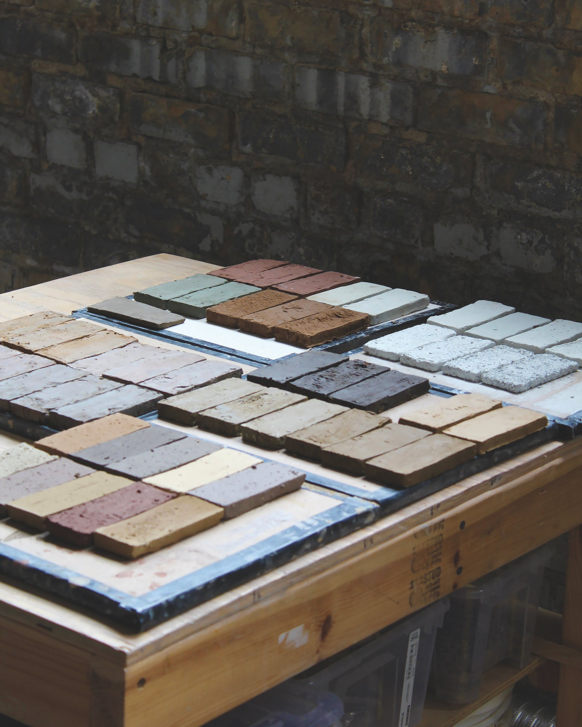 Array of raw clay samples on a wooden studio table
