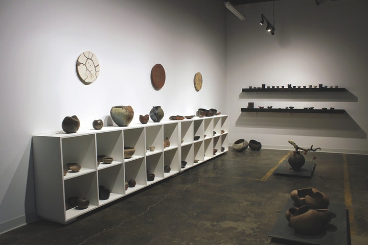 Minimal dimmly lit ceramics gallery with various vessels on display