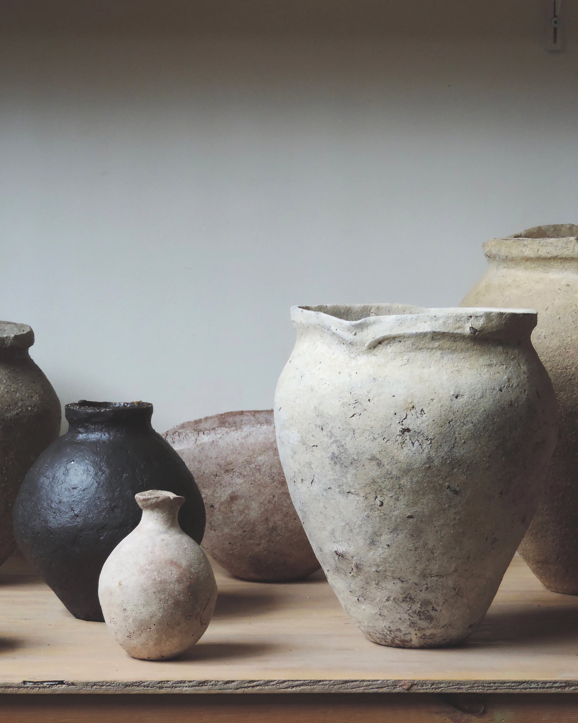 Series of textured ceramic vessels on wooden table