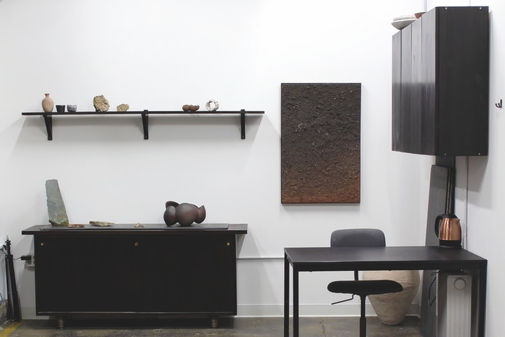 Minimal office space with black furniture and various ceramic pieces on display