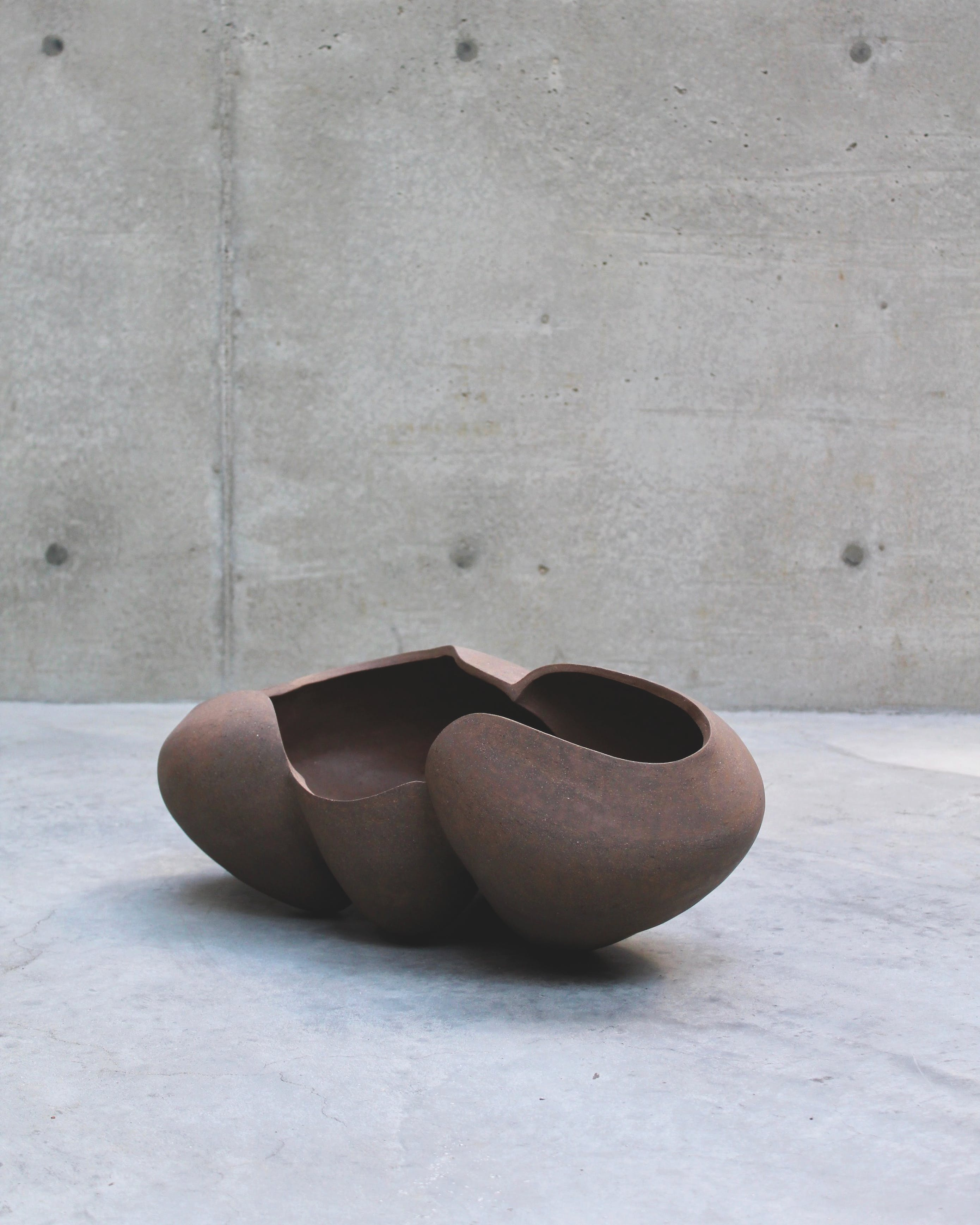 Smooth brown ceramic vessel on concrete surface