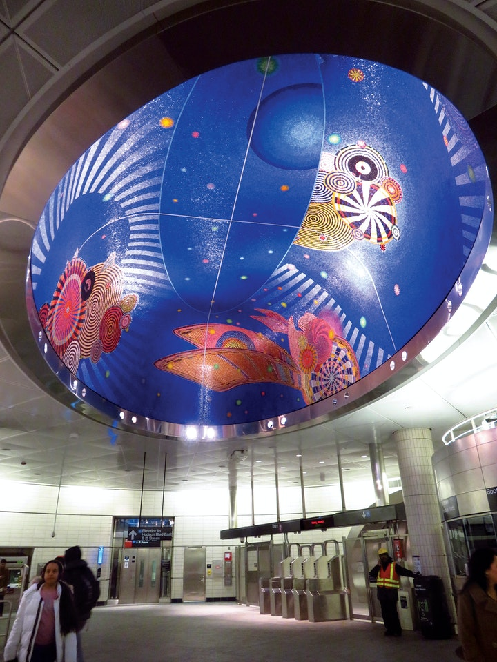 Transit station ceiling art featuring crocheted mandala designs on a blue background