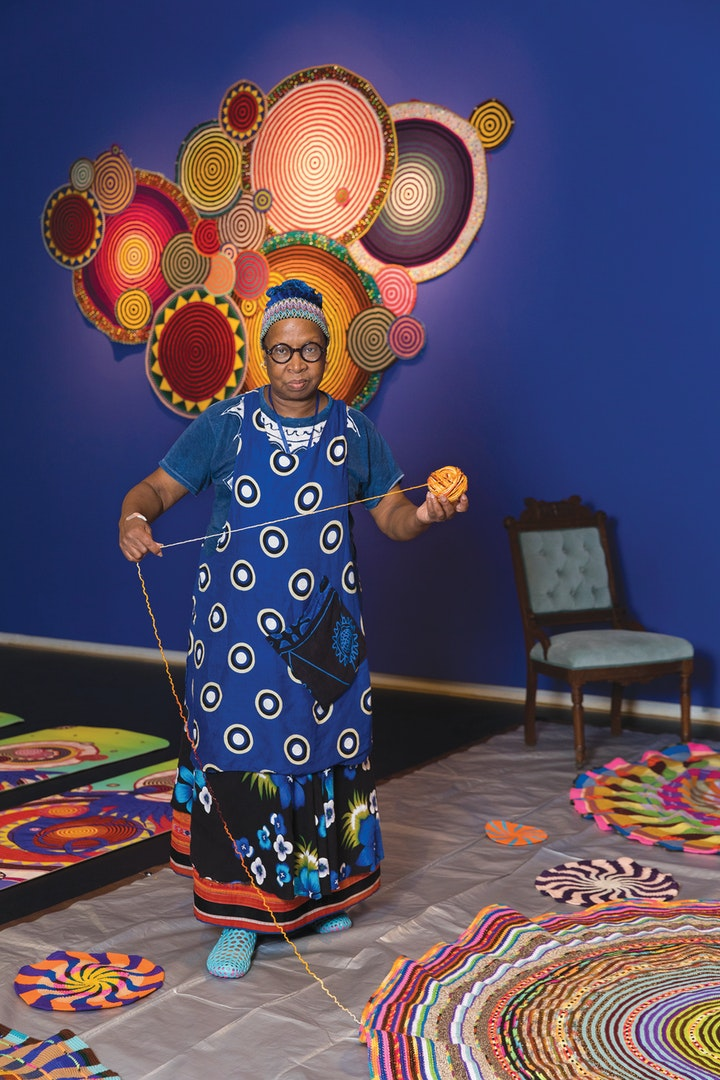 Artist creating large colorful crochet artwork with finished work on blue wall in background