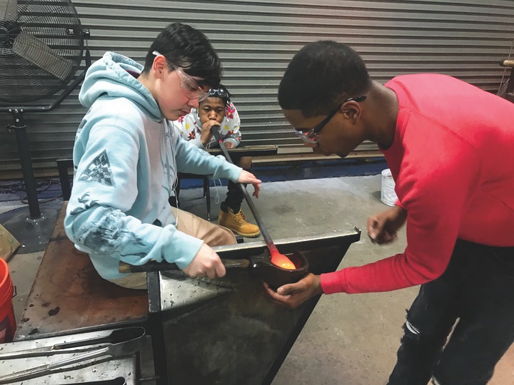 Three young people working together on a blown glass project