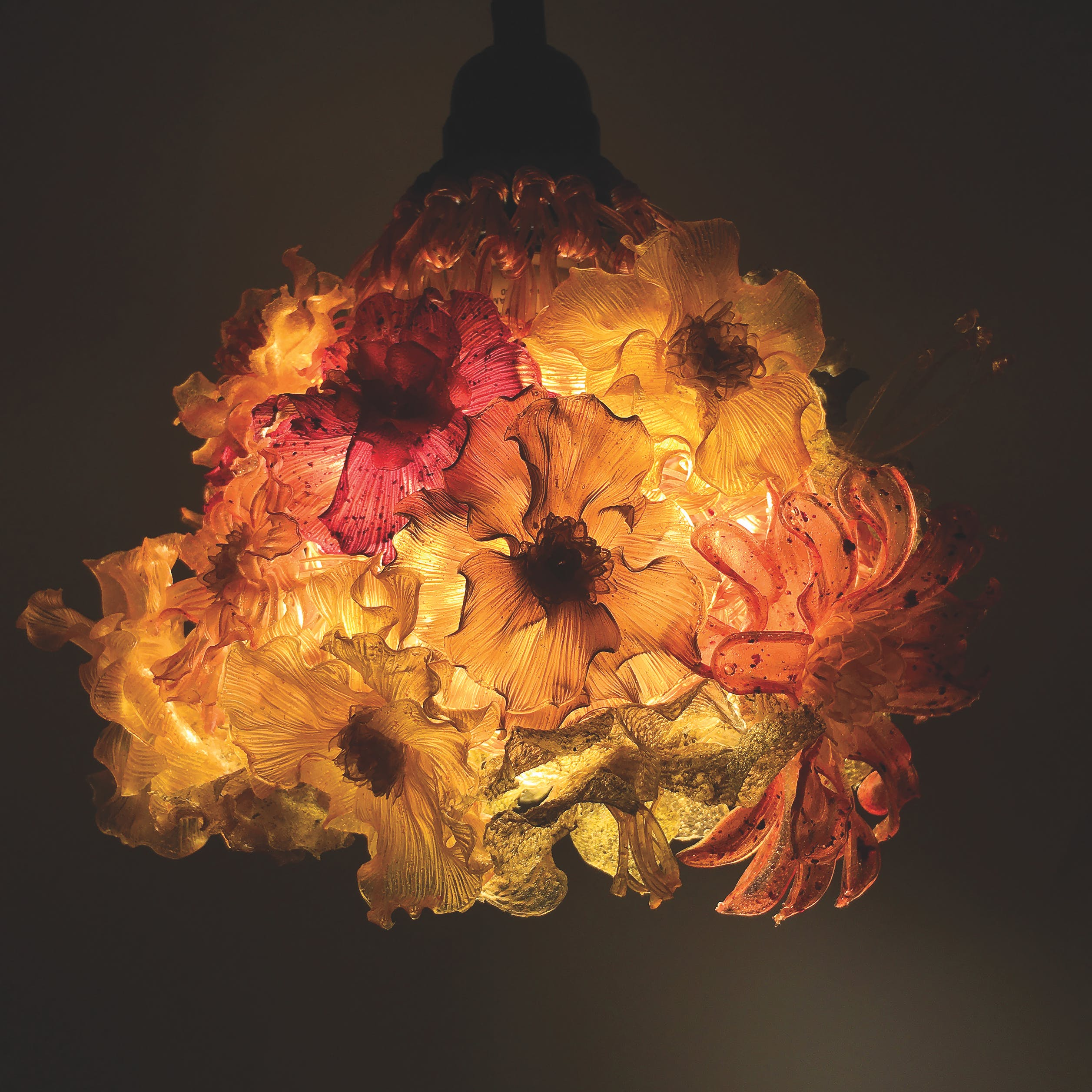 Illuminated lampshade covered with flowers made from agar in a dark setting