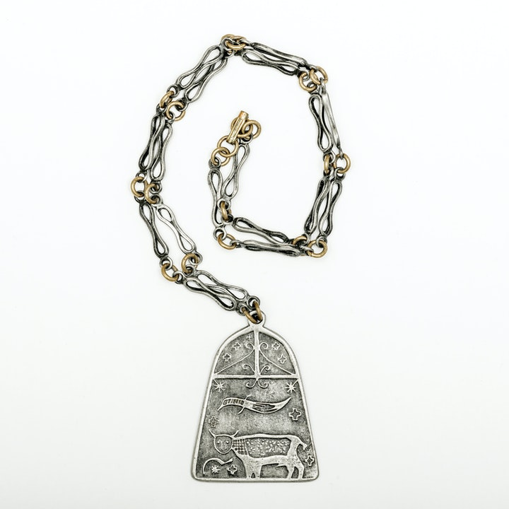 Engraved pewter pendant on a silver and gold chain