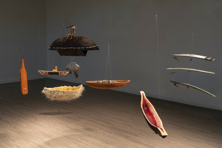Empty room with various wooden sculptures hanging like a mobile