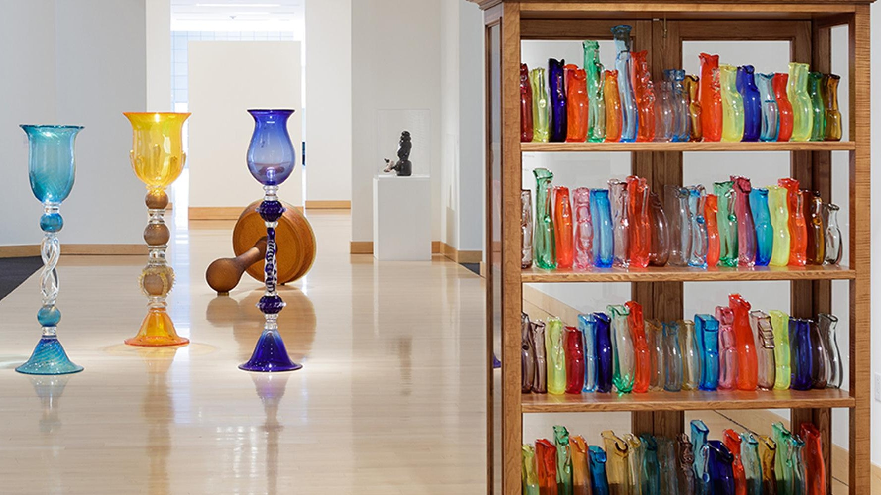 Room in a museum filled with colorful glass artwork of different sizes