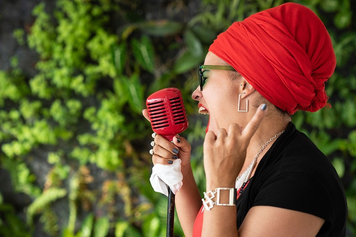 Singer with red headwrap singing into a red microphone