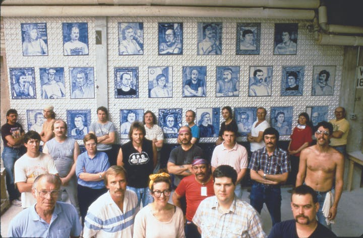 1991 photo of factory workers and an artist posing in front of a wall of ceramic paintings