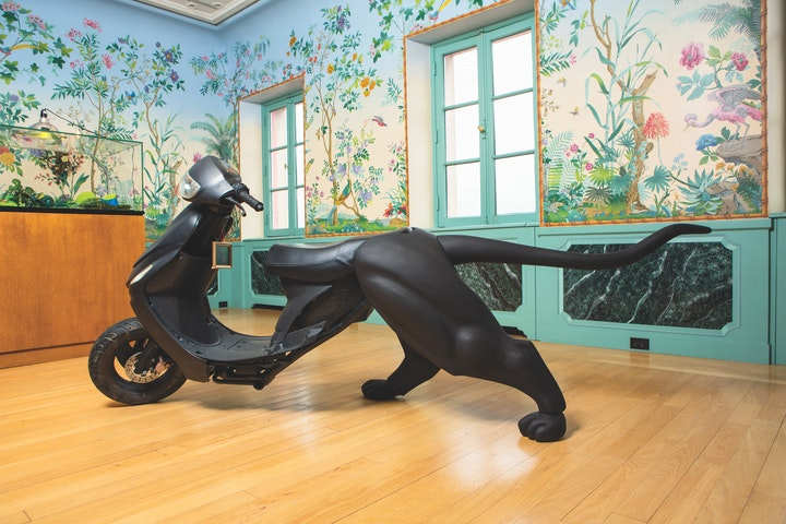 Sculpture with the front half of a black moped and the rear half of a black cat made from wood displayed in a room with playful ways and windows