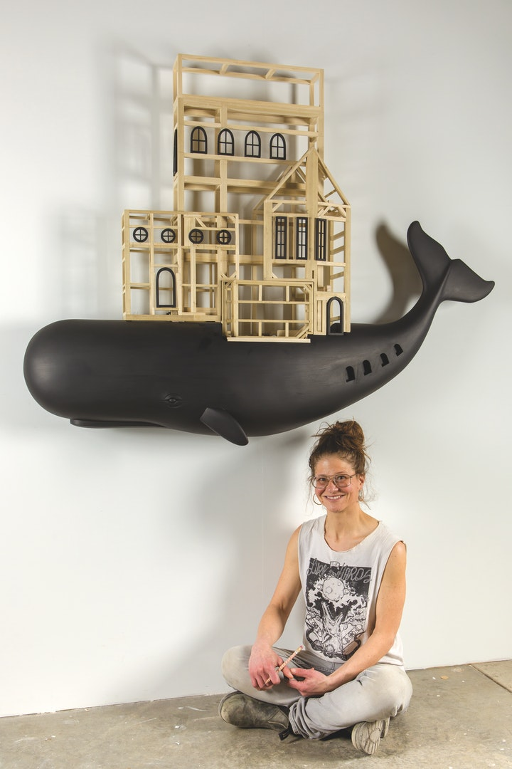 Artist sitting beneath a wood sculpture of a black whale with a building on its back