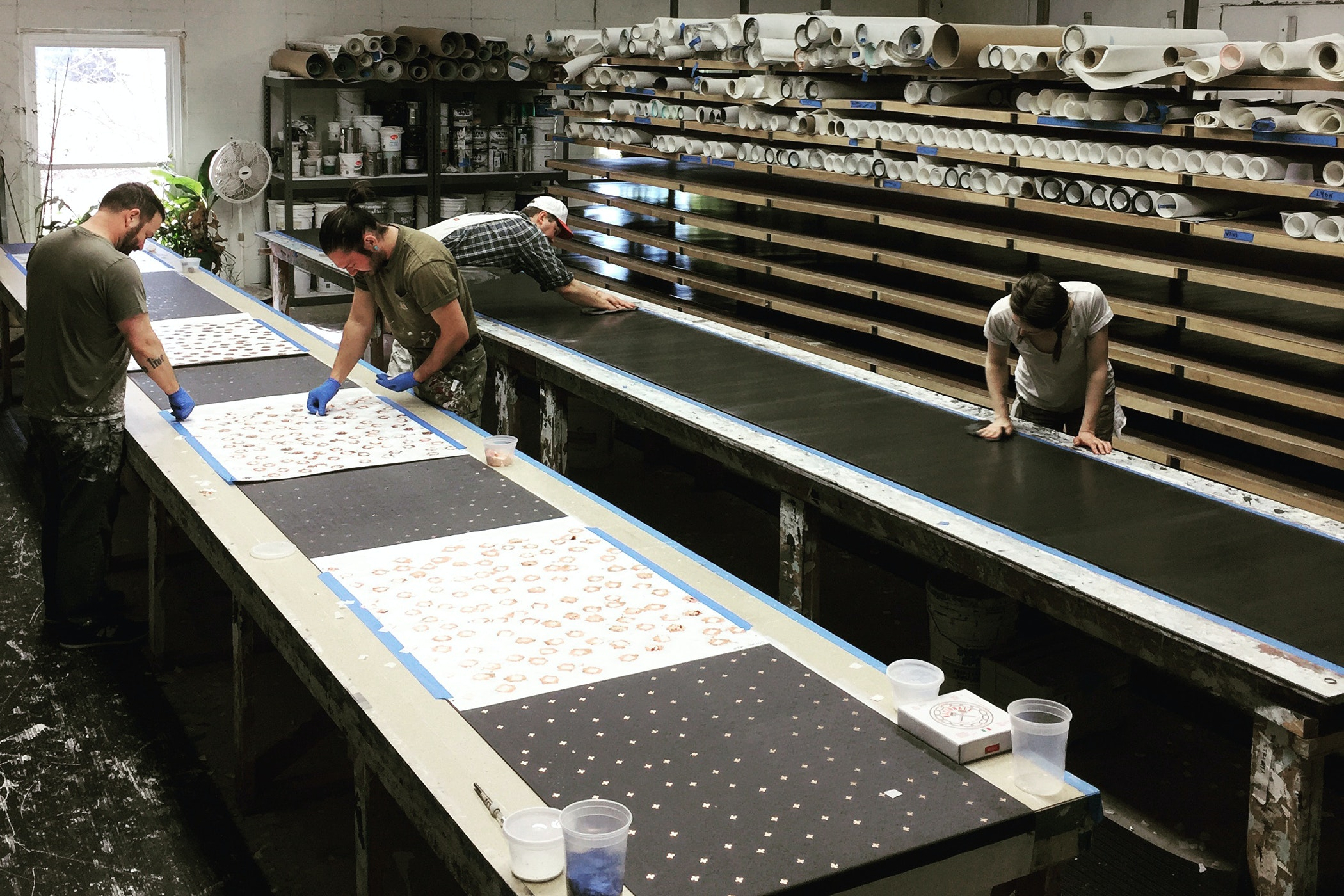 Group of artists working paper projects on two long craft benches in a studio room