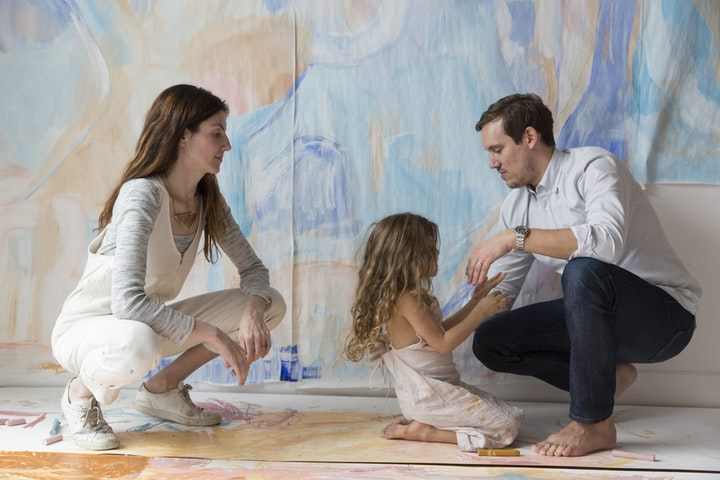 Two older people and a younger child posing together in room with handpainted paper