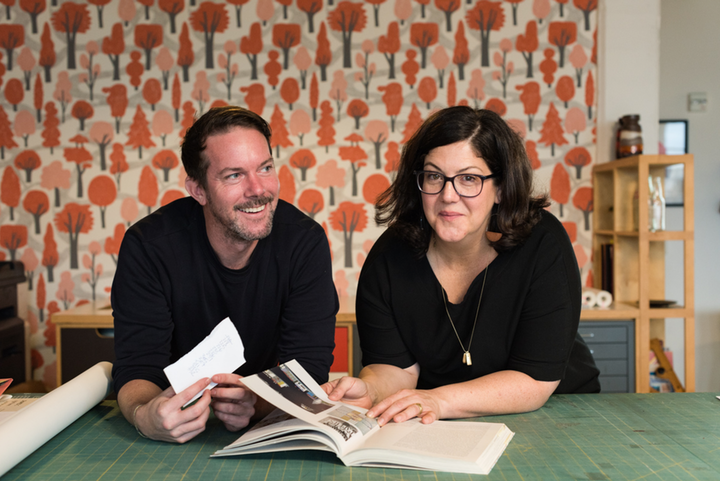 Two people sitting at a craft able with books and paper samples in front of wall with a vibrant wallpaper