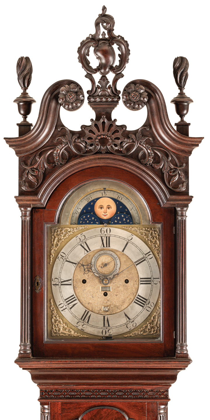 Top of an ornately carved antique case clock made of dark wood