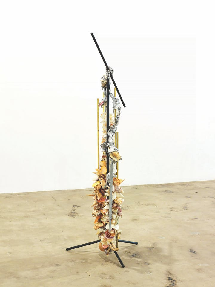 Sculpture made from mic stand laden with seashells and other miscellaneous debris