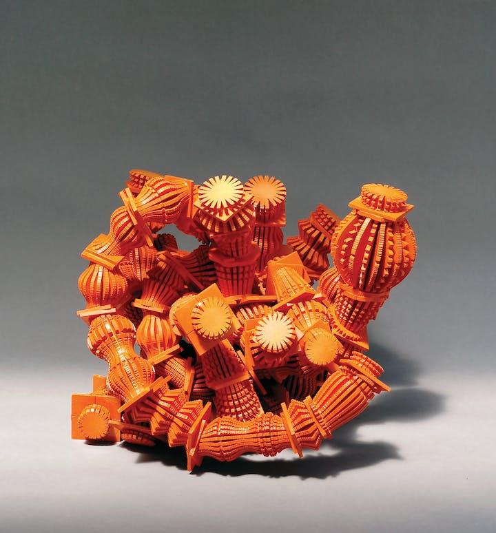 Orange tangled wood sculpture reminiscent of a sea creature