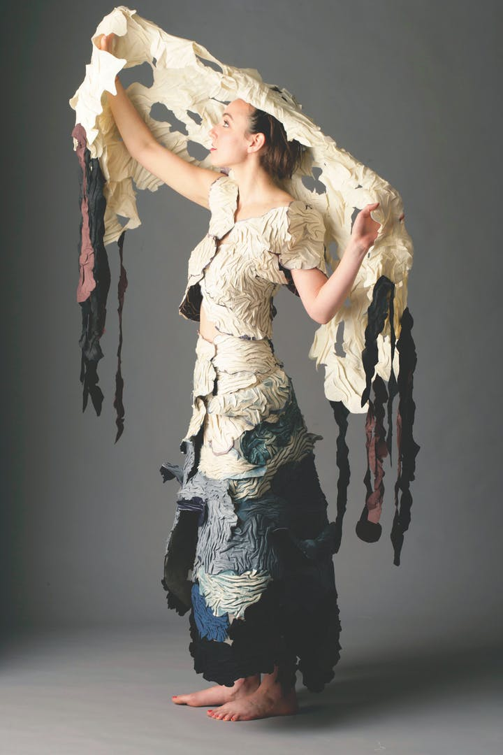 Woman in textured dress inspirted by an ocean oil spill holding up a matching shawl