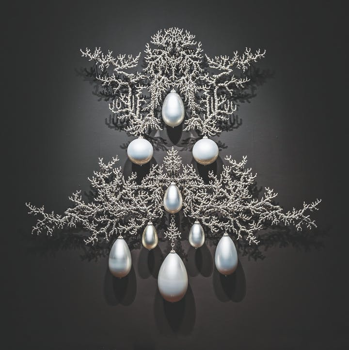 Metallic sculpture on black wall with large hanging pearls amidst fine crusty branches
