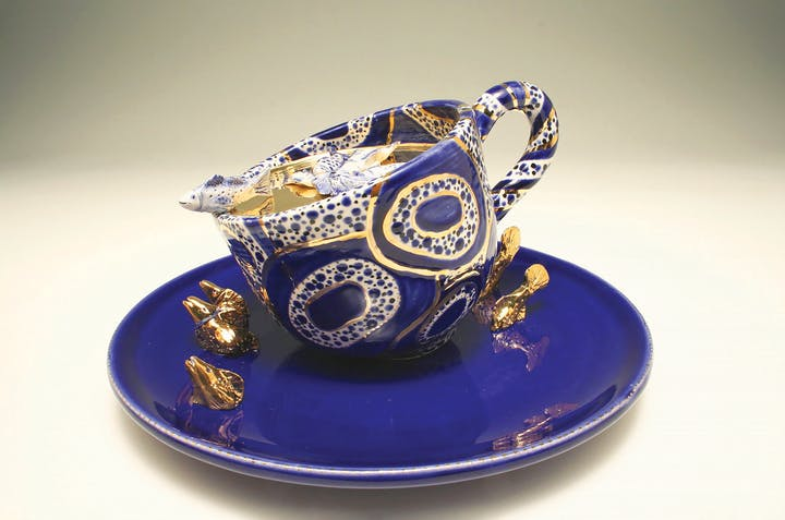 Blue teacup with gold patterning with a fish tipping out of it