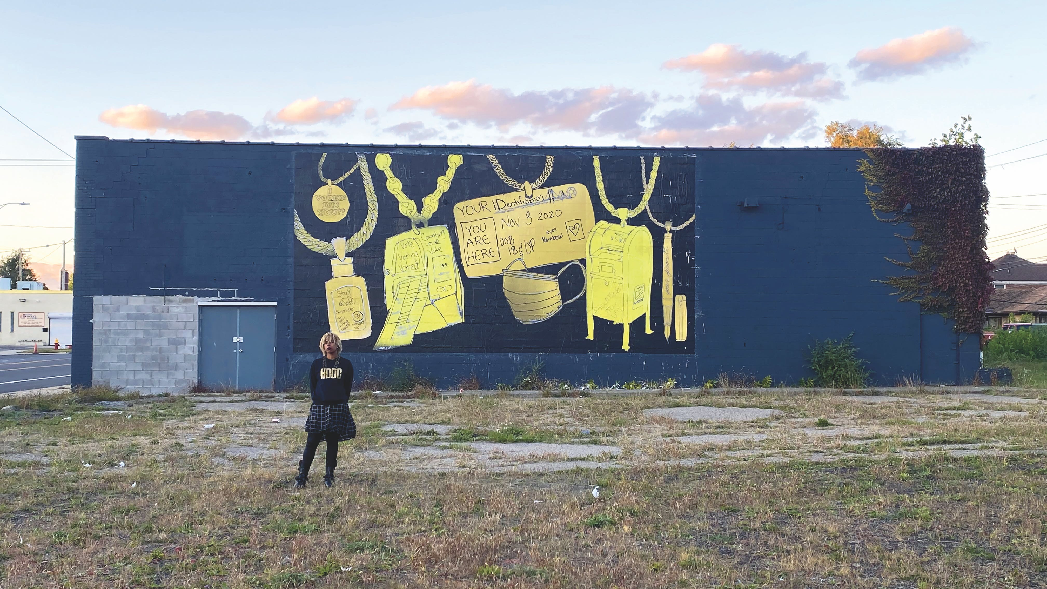 Person standing in empty urban lot with dark blue building behind them featuring a mural with yellow and gold images of various adornments