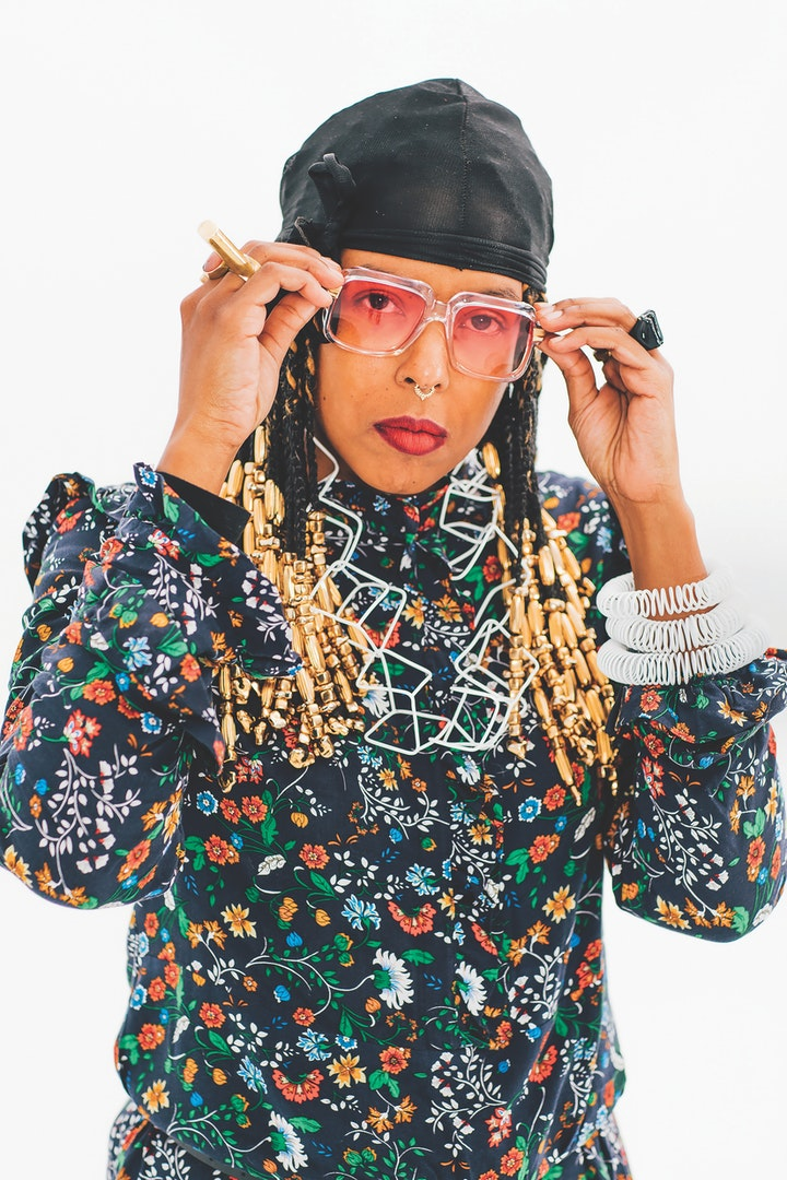 Portrait of Tiff Massey in floral patterned shirt and black cap white necklace and bracelet adjusting pink shaded sunglasses
