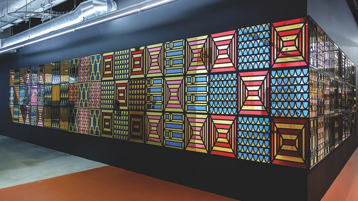 black wall adorned with large tiles of various quilt patterns in red yellow pink and blue