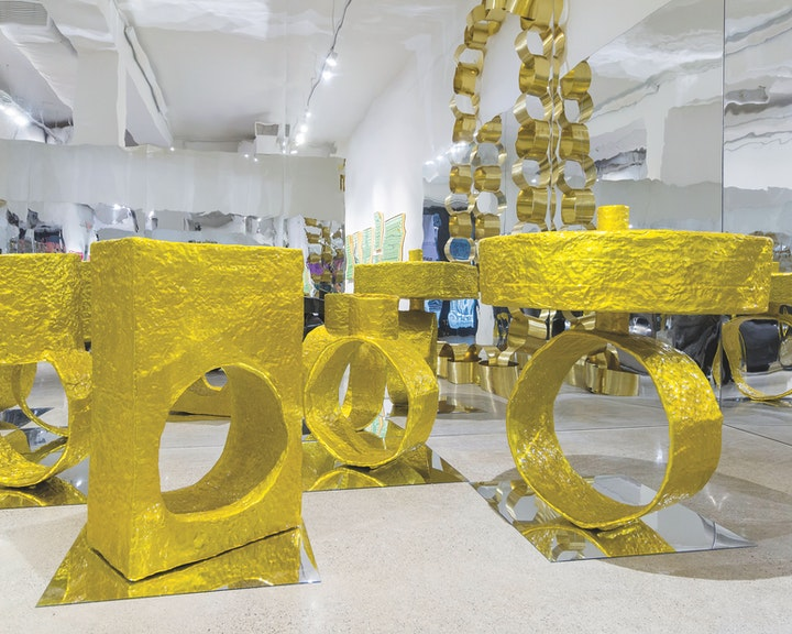 Exhibition floor with gold rings the size of statues surrounded by mirrors
