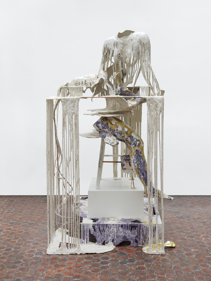sculpture with the outline of person made from dripping plaster on a pedastal above a purple and gold mottled leg