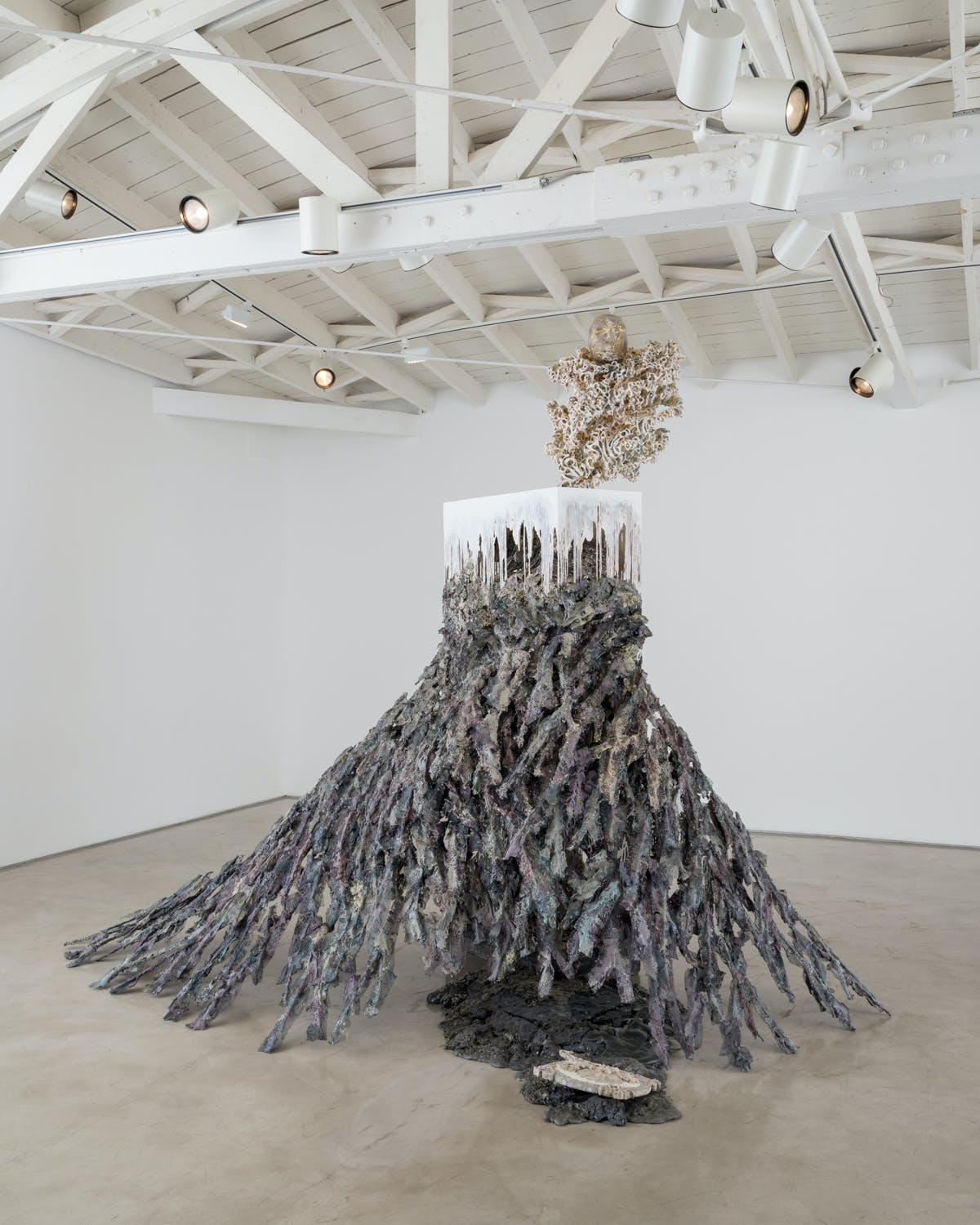 sculpture reminiscent of the base of a fir tree except purple gray and topped with dripping cube coral skeleton and a face