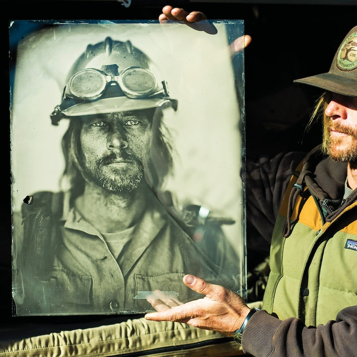 portrait of firefighter holding up an ambrotype portrait of himself