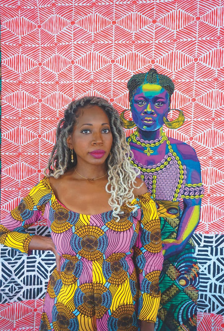 woman in colorful patterned clothes standing in front of a colorful patterned quilt featuring a portrait of a woman