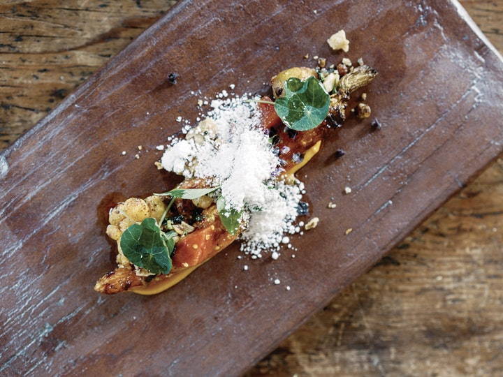 artistically designed vegetable nut and grain dish served on a brown stoneware plank