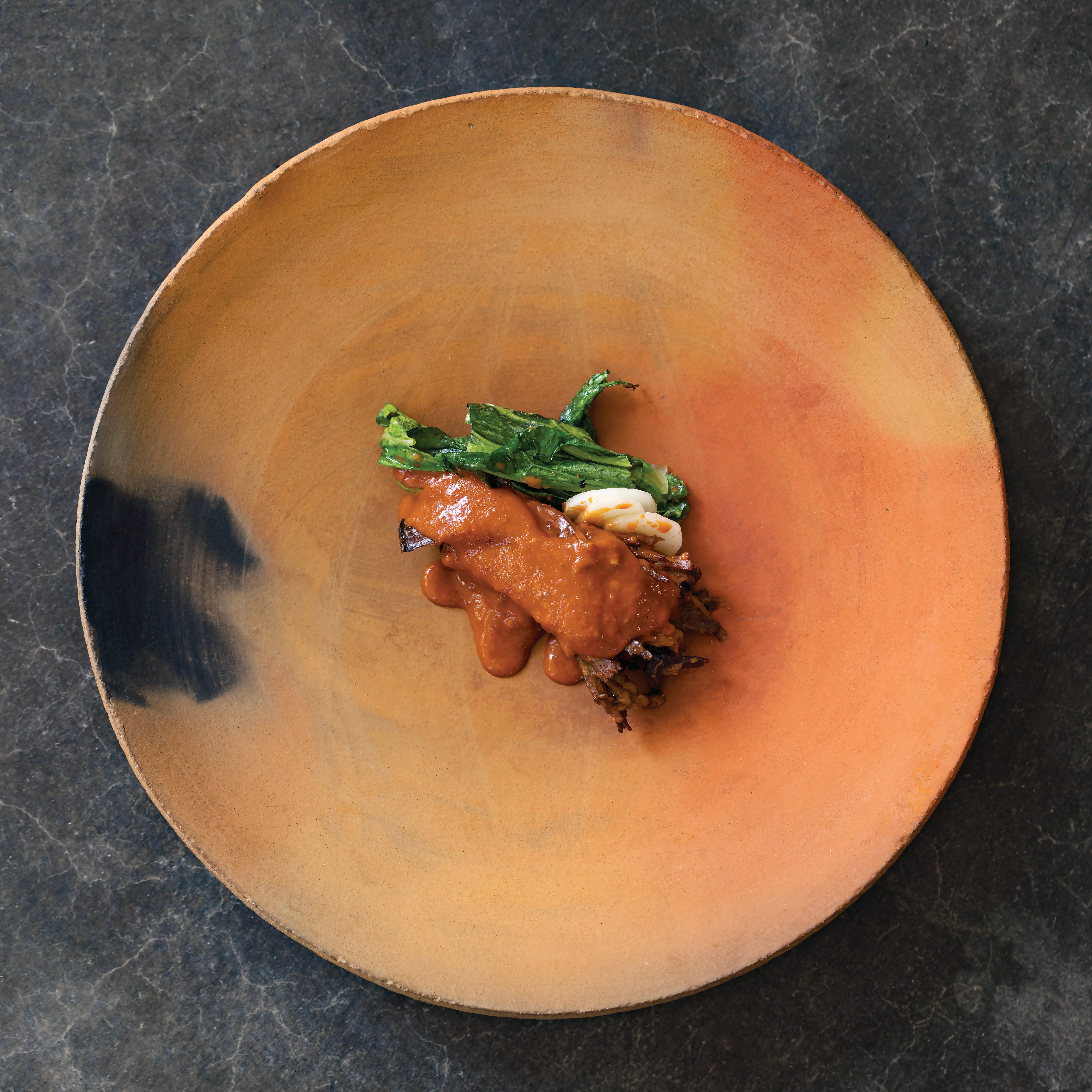 smooth orange plate with smoke smudge with artistically designed saucy beef dish in the center