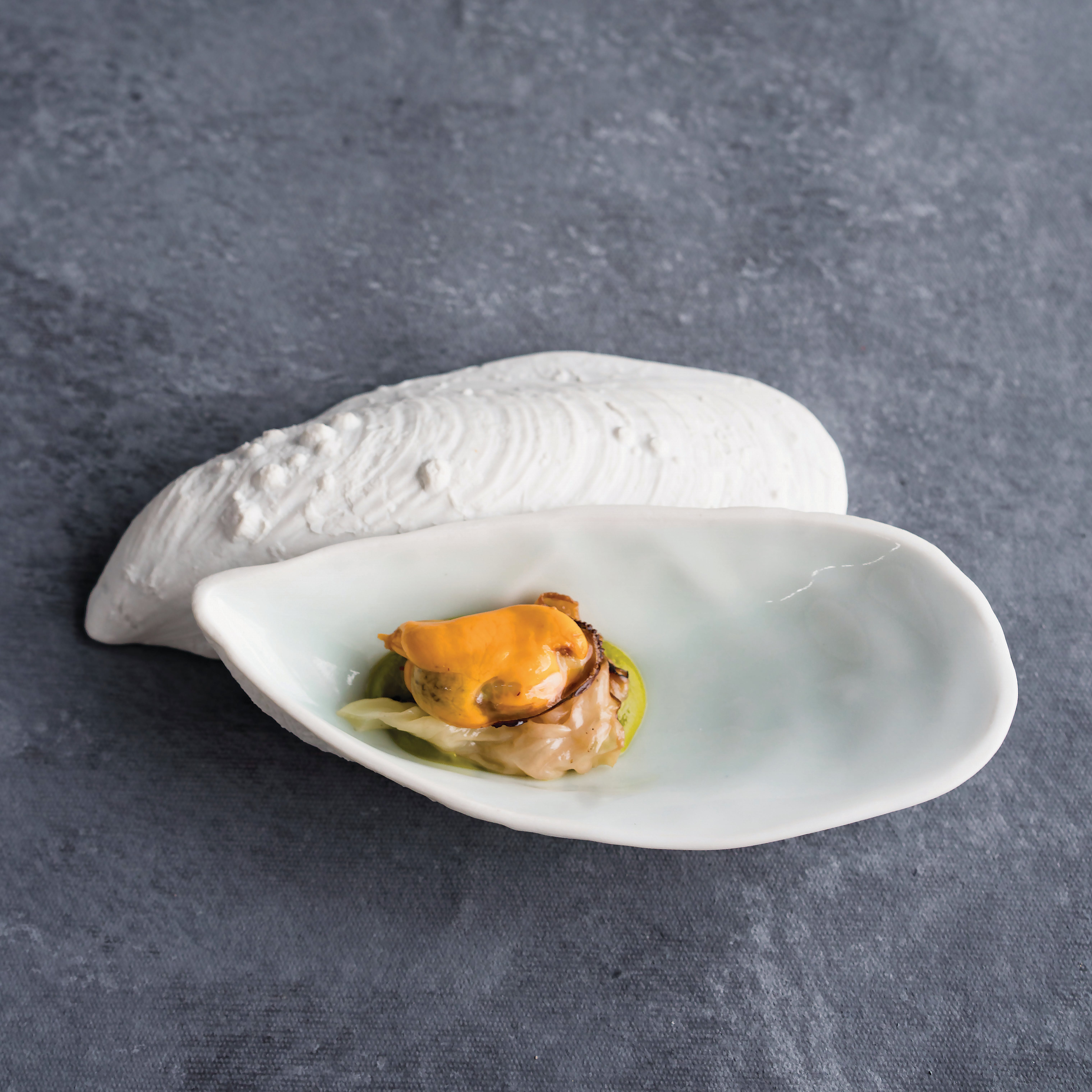pair of small white ceramic plates replicating a mussel shell and serving a small mussel dish