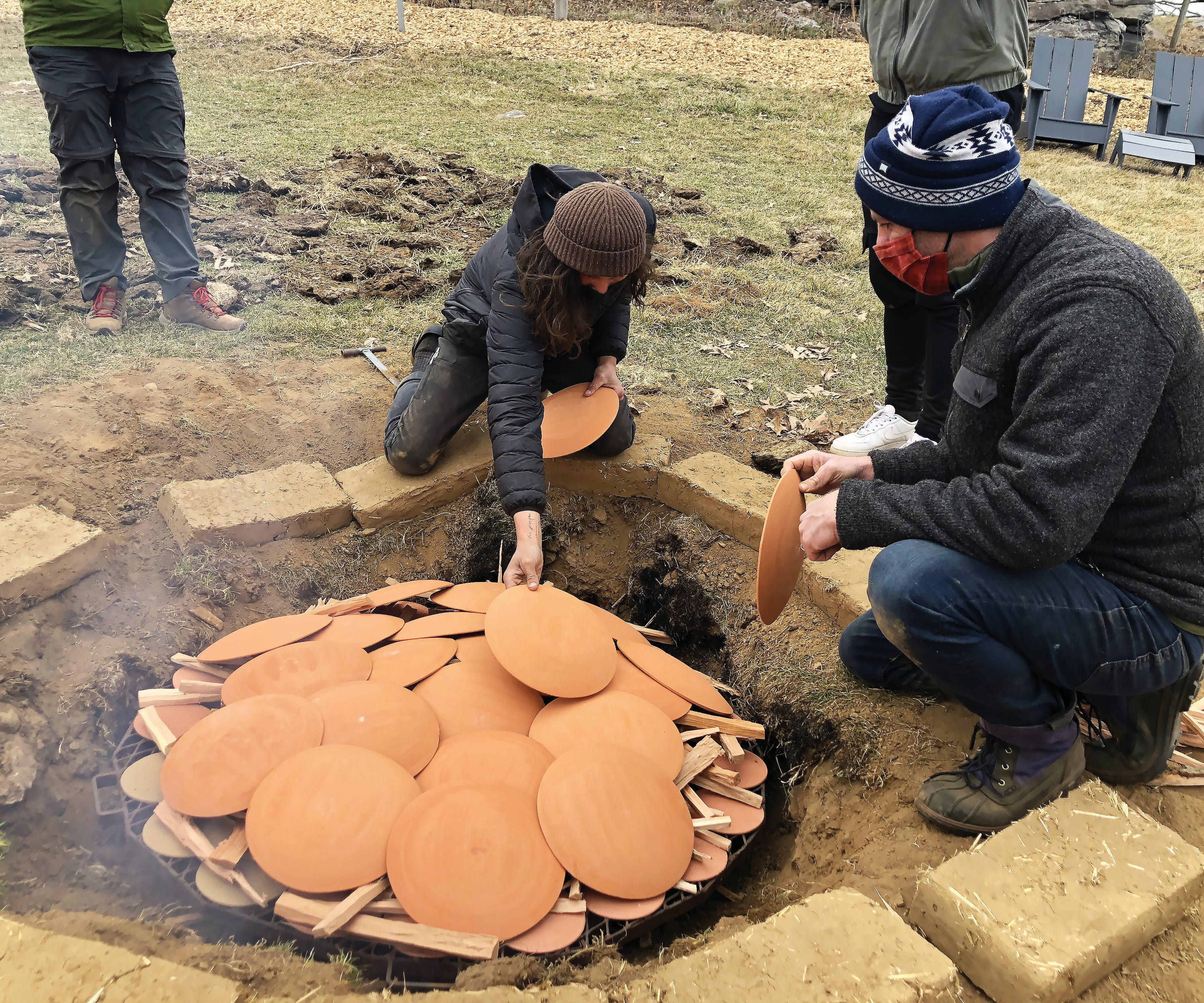 two crouched people in jackets hats and masks stacking clay plates over wood to prepare a buried pit fire