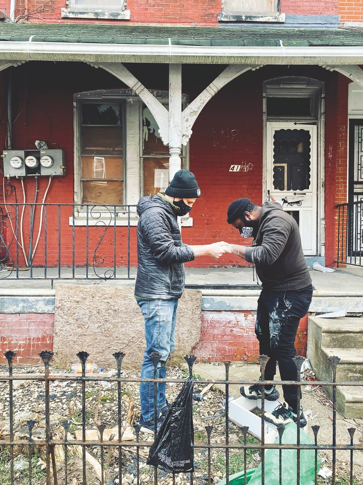 Two people making a plaster cast outside in a yard in front of a red brick house with boarded windows on what appears to be a chilly day
