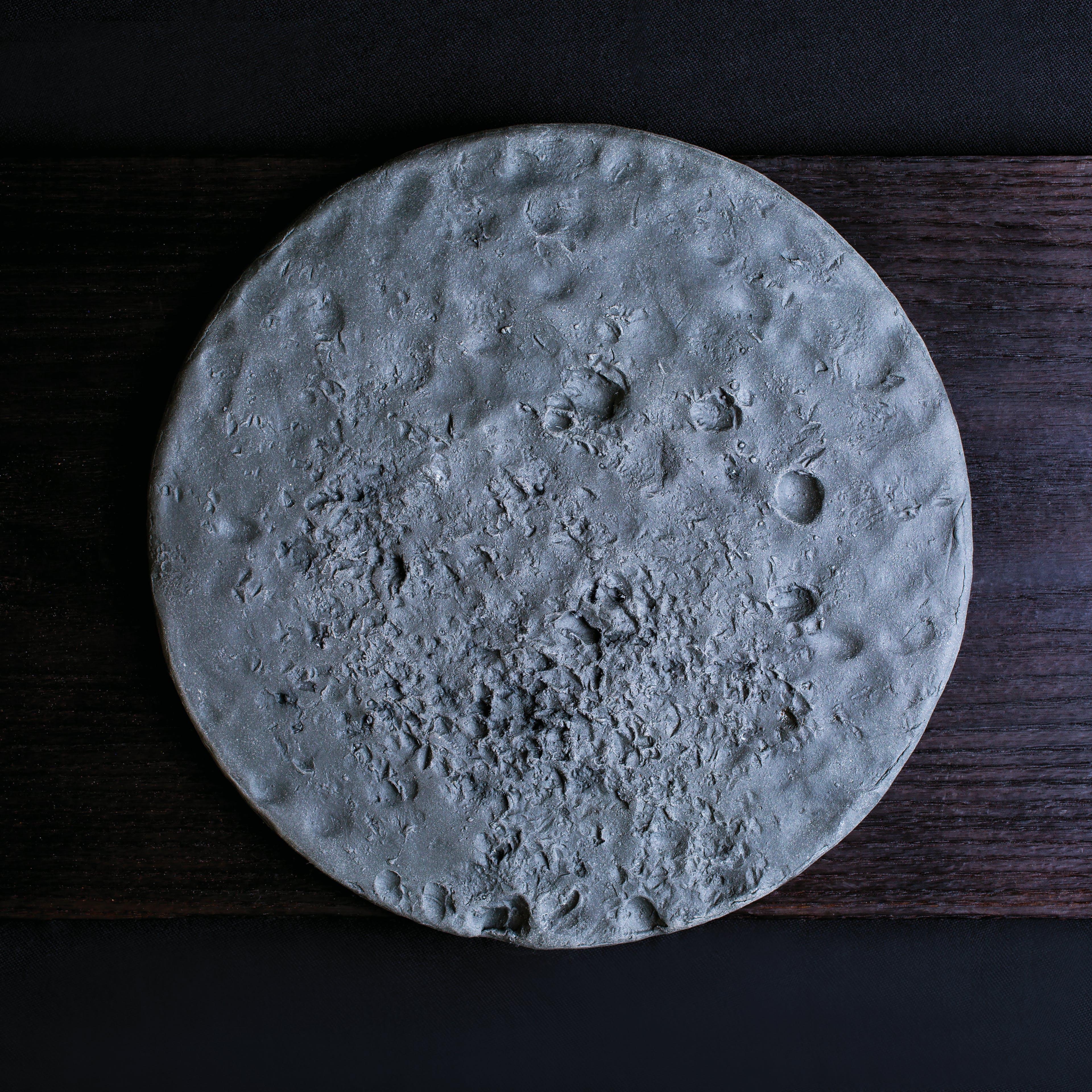Gray round pocked ceramic plate on wood planks