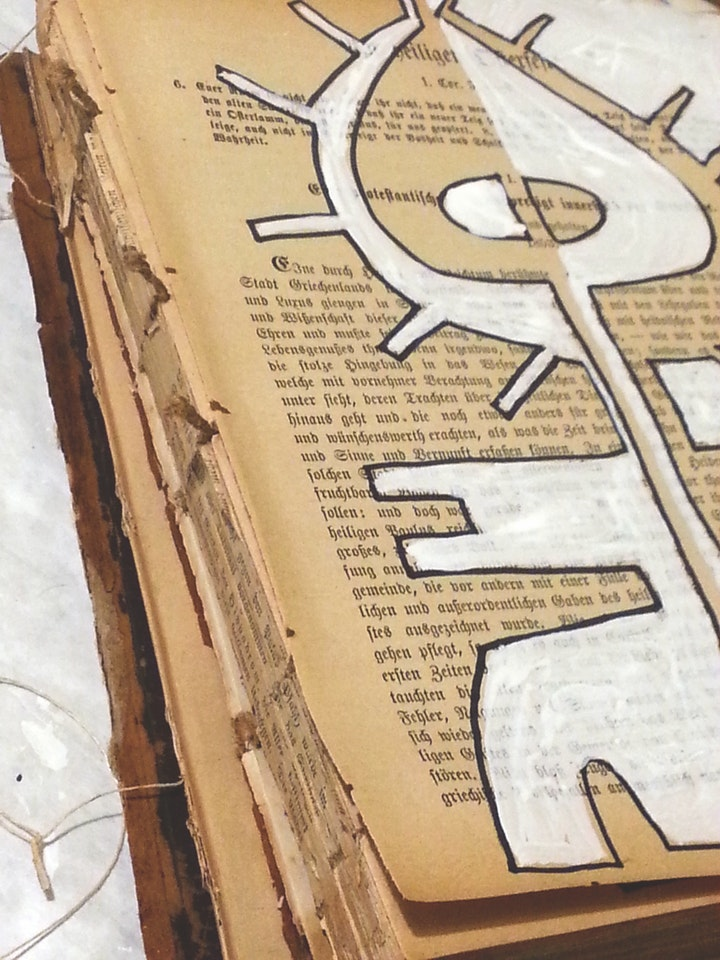 dismantled antique book with painting of a symbol over the topmost page