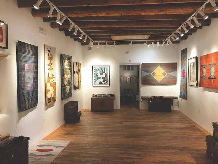 view of the inside of a small art gallery with wooden floor and cream walls and weavings and paintings on display