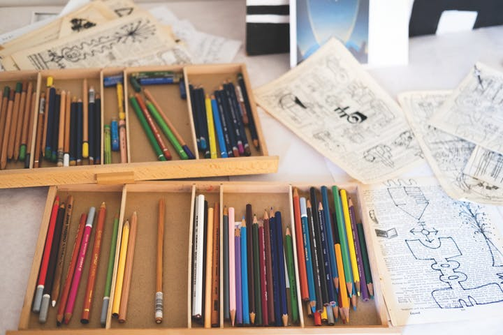 pencils in trays next to drawings on book pages
