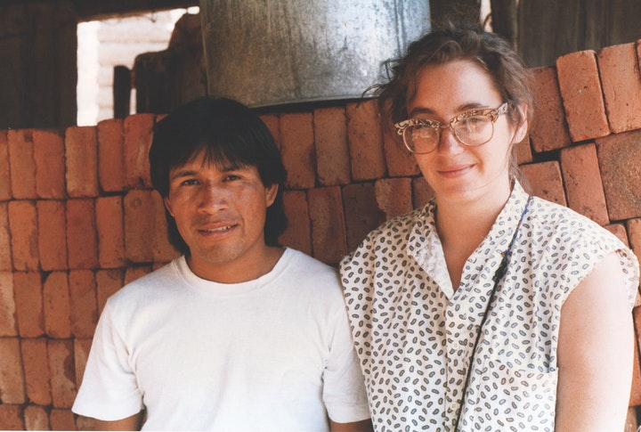 vintage portrait of a young man and woman sitting against a loosely stacked red brick wall